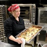 New Kitchen of Opportunities chef Michelle Spieker removes vegetable lasagna from oven