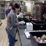 A Kitchen of Opportunities volunteer helps pack meals